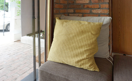 throw cushion: Generic yellow pattern pillow on armchair with brick background