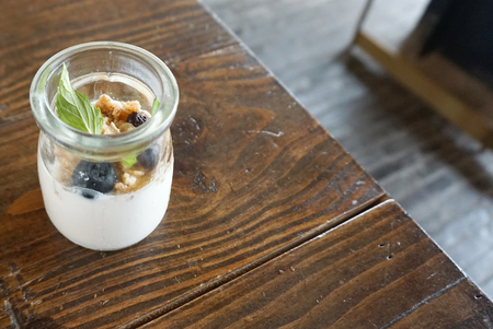 homemade yogurt with blueberry and granola in  small jar on timber table