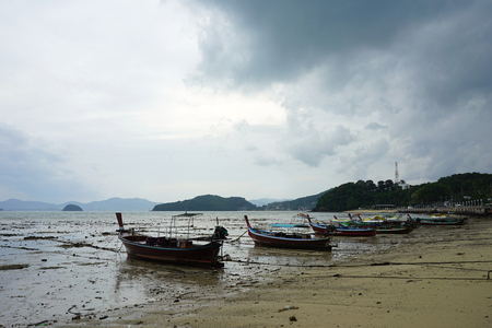 Fisherman boat parking on the lower tide beach with the dull sky background in Phuket