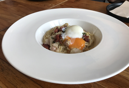 Closed up of spaghetti carbonara with soft-boiled egg on top on white bowl on timber table