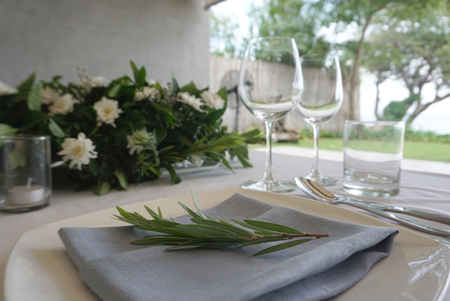 Dining set on the white table sheet with white bouquet flower and grey wall background