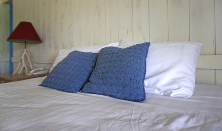 Comfortable navy color throw cushion on white pillows on the bed with white stained timber plank background