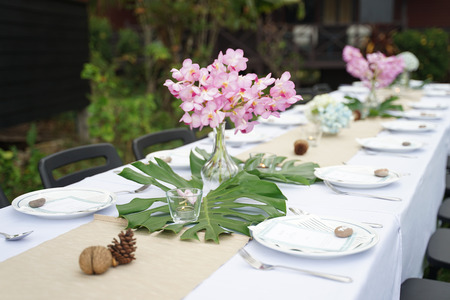 Dining set on the white table sheet with beautiful bouquet flower outdoor and green background 版權商用圖片