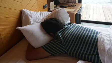 Asian man wearing stripe T shirt sleeping on the white bed with his face down in the bedroom Banque d'images