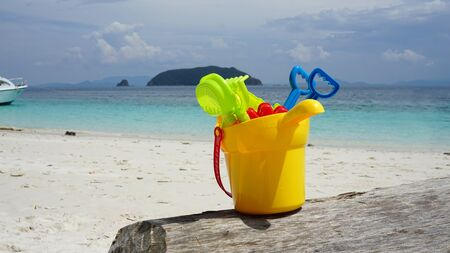 Colorful kid sand scoop toy in yellow plastic bucket on the timber log with beautiful beach and blue sea background Фото со стока