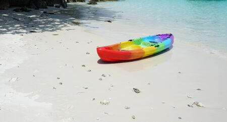 Colorful Kayak boat on the sand outdoor with beautiful beach and blue sea background Фото со стока
