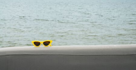 Yellow vintage sunglass on the chair with sea background                             Stock Photo