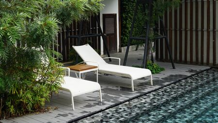 White chaise lounge on timber deck next to mosiac pool surround by green plants outdoor                         写真素材