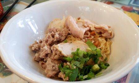 Dried egg noodle Thai style with minced pork and fish ball serving on white bowl 版權商用圖片