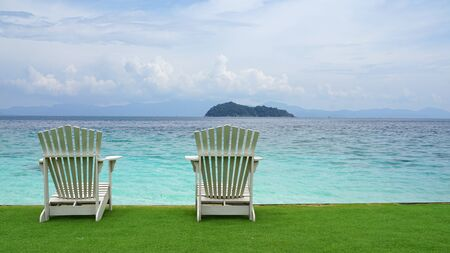 White vintage timber seating on the green grass with beach and ocean background