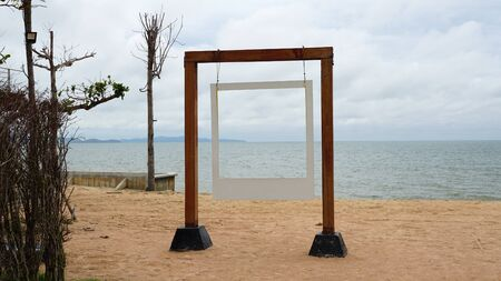 White picture frame hanging on the timber pole with sea and beach background