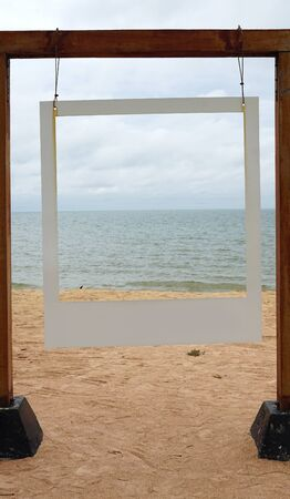 White picture frame hanging on the timber pole with sea and beach background        版權商用圖片