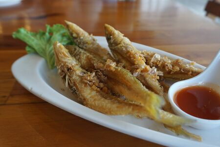 Deep fried small fish with garlic serving with chli sauce on white plate