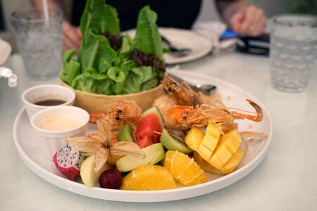 Deep fried shrimp serving with fresh salad and variety of fruits with salad dressing on white plate