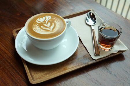 Close up hot coffee latte on white coffee cup sering with brown sugar syrup on timber table background 版權商用圖片