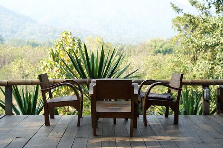 Solid teak timber lounge chair set on the terrace with mountain background