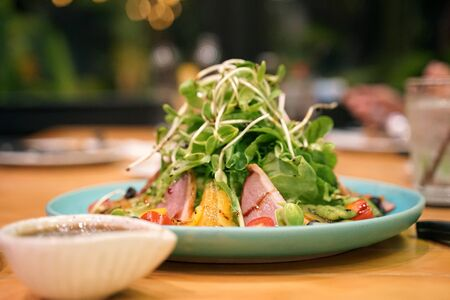 Smoked duck breast rocket leaves salad and fresh orange and tomato serving with orange sauce on dining table