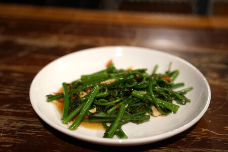 Stir fried Chayote leaves with chili in Oyster sauce on white plate on timber table