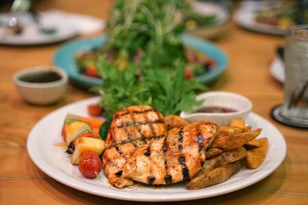 Barbeque grilled chicken breast and fried potato chip serving with fresh salad  on timber table