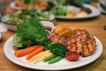 Healthy grilled vegetable and fresh salad serving with Barbeque grilled chicken breast steak on timber table