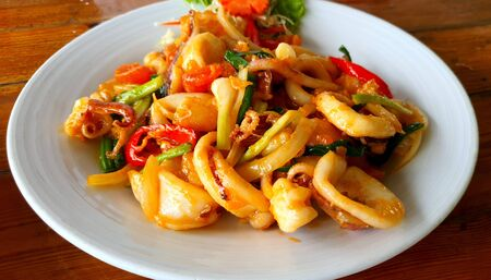 Stir fried fresh squid with eggs with yolk sauce with chilli and onion on white plate 版權商用圖片