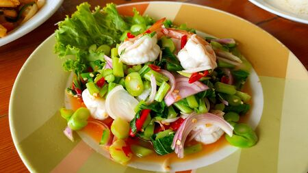 Shrimp spicy salad with green kale Thai style serving on green plate