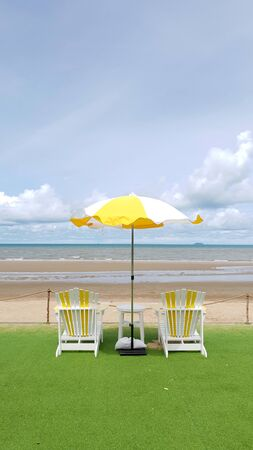 Yellow and white color seating and parasol onthe green lawn with beach and sea bakground