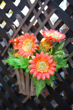 Colorful of beautiful red - orange cloth artificial flower wiht green leaves on lath , Close up Stock Photo