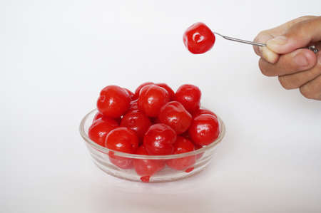 Hand pick up maraschino cherries in a glass bowl with a silver fork isolated on white background