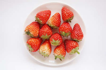 Close up of photo of very fresh havested red strawberries on white plate isolated on white background