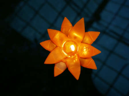 Colorful flower candle in orange color floating on water