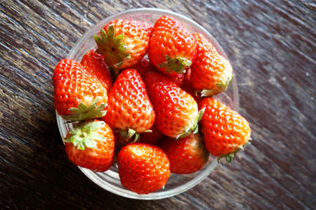 Close up of photo of very fresh harvested strawberries in glass bowl on wooden background