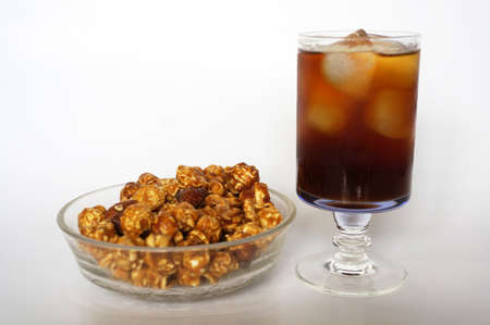 Caramel popcorn on white plate and cola on champagne glass isolated on white background