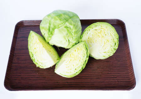 Close up of photo of very fresh green cabbages and slice cabbages on wooden tray isolated on white background
