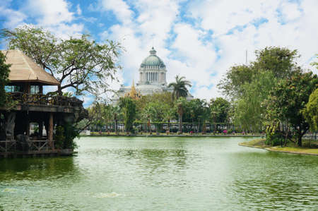 A photo of landscape of a pond at public park with Ananta Samakhom Throne Hall in scenery under the blue sky, Thailand