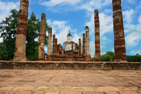 A photo of ruin of Buddha and stone pillar under the blue sky, is a World Heritage at Sukhothai Historical Park, Sukhothai, Thailand (Thai alphabet in the picture means Dont climb.) Stock Photo