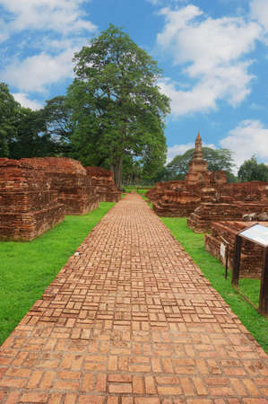 A photo of brick walkway at the ruin under cloudy sky, is a World Heritage at Sukhothai Historical Park, Sukhothai, Thailand Stock Photo