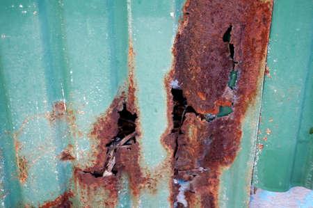 Een foto van groen galvaniseert Bladsamenvatting met een gat van roesttextuur en achtergrond, omhoog sluit