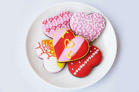 Love Heart Cookies: Chocolate cookies decorated with various color of sugar topping on white plate isolated on white background.