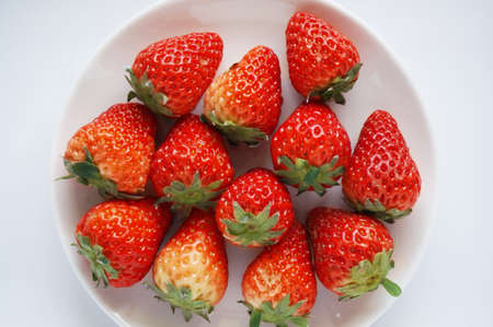 Close up of photo of very fresh harvested strawberries on white plate isolated on white background
