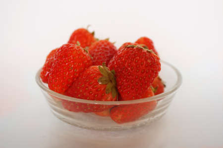 Close up of photo of very fresh harvested strawberries on glass bowl isolated on white background