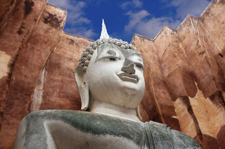 A photo of Buddha Sitting against the wall under the cloudy sky, is a World Heritage at Wat Sri Chum temple, Sukhothai, Thailand
