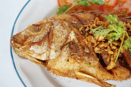 Asia - Asian eating food, Thai food, fried Nile tilapia river fish ( Oreochromis niloticus ) with garlic, coriander, and slice of tomatoes, close up
