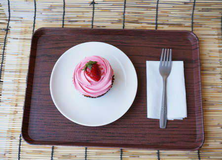 A photo of colorful cream strawberry cupcake decorated with strawberry topping on white plate on wooden tray on rattan curtain background, close up