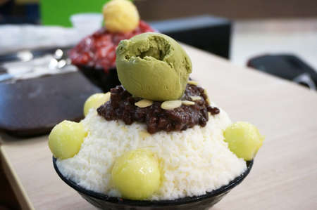 Asia-Asian food, Bing su: Korean shaved ice dessert with sweet toppings, melon, red bean and green tea ice-cream in black ceramic bowl, close up Stock Photo