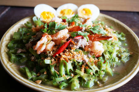 Asia-Asian eating food, Thai foof, Yum Tua Poo: Spicy Shrimp and betel nuts salad or Winged bean salsa, with boil eggs isolated on white background, close up
