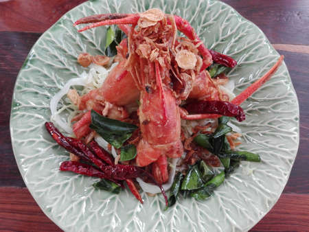 Asia-Asian eating food: Crispy shrimp with sweet tamarind sugar sauce. Decorated with fried chili and Kaffir lime leaf, crispy onion on a plate on wooden background, close up