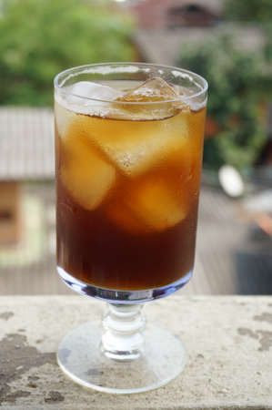 Cola, black coffee, on champagne glass on balcony of an old building, close up