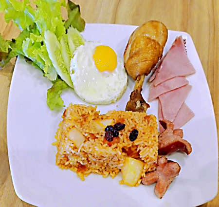 Asian food, Thai food, American Fried Rice with cucumber, chicken, ham and sausage on white plate on wooden background