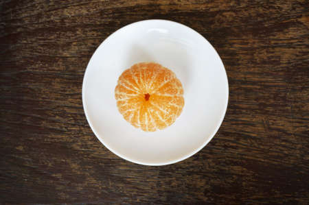 Close up of photo of very fresh peeled orange on white plate on wood table background